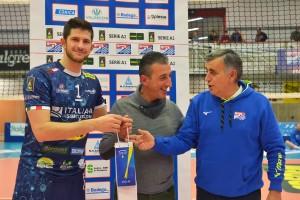 il capitano Buzzelli premia lo spettatore che ha indovinato il punteggio del primo set con l\'olio tipico Tuscania